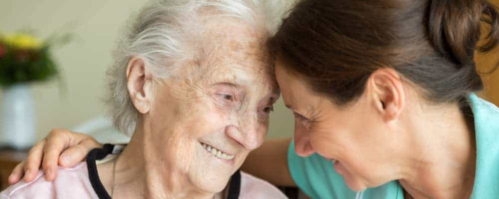dementia caregiver assisting senior woman at home